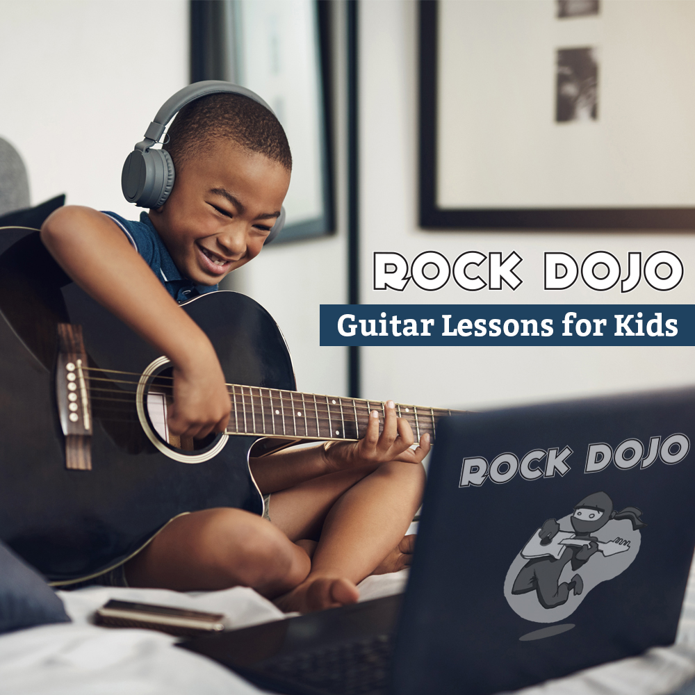 african amaerican kid learning to play guitar with Rock Dojo Guitar Lessons for kids